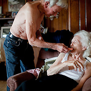 "Bernard Triplet tries to put Mary's dentures back in her mouth. Because of Mary's deteriorating memory, she forgets she has false teeth and them out thinking she's choking on food.  Bernard hunts endlessly for them because they are expensive to replace and he insists that she wear them because, ""She looks so much prettier when she wears them."""