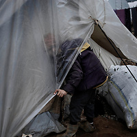 SYRIA, ATMEH. A child is about to enter the tent of his family in the camp for displaced Syrians in Atmeh on January 12, 2013. The camp is on the border with Turkey and is providing shelter to nearly 13,000 people; most of them are children. ALESSIO ROMENZI