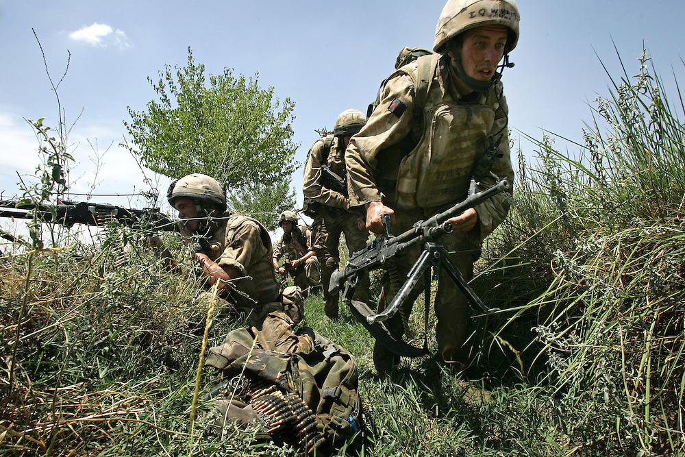 29/06/07..Sangin Valley, Helmand, Afghanistan..Soldiers from A Company 1 Battalion Royal Anglians, known as 'The Vikings' move along a ditch as other members of their unit provide covering fire whilst conducting operations against the Taliban in the Sangin Valley, Helmand province, Afghanistan on the 29th June 2007...The soldiers made a Tactical Advance to Battle over night carrying just food, water and ammunition. At first light they moved on their objectives; a series of compounds, orchards and paddy fields. During the day they exchanged fire with the enemy on a number of occasions. 13 Taliban were killed, 1 British soldier and 3 Afghan troops were wounded...