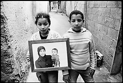 Niveen and Ihab Ghanem, the children of Manal Ghanem, pose with a photograph of their mother taken from inside an Israeli prison. In 2003, Israeli forces arrested Manal and sentenced her to prison where she gave birth to a son, Nour.