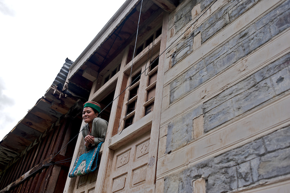 A Kinnauri woman looks from the window of her home in the village of Giabong, Himachal Pradesh, India