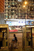 Disabled man passing by phone-boxes in Kowloon.