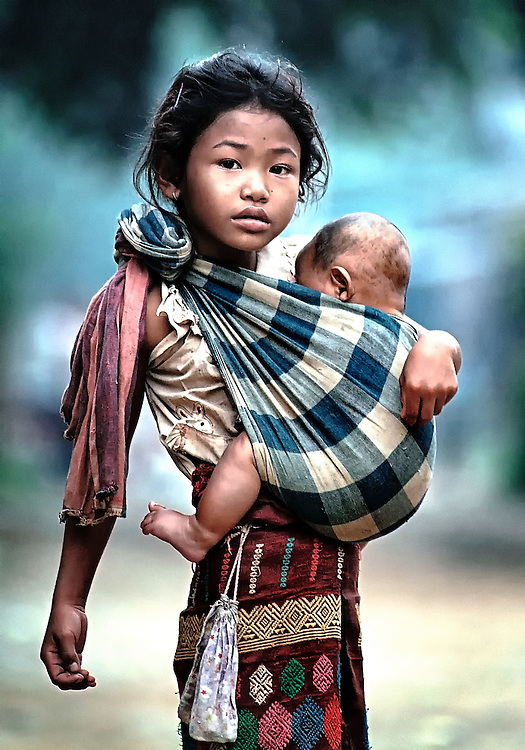 A girl taking care of a baby in Luang Prabang, Laos.