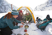 Erica Koltenuk, Christian Fritze and Kate Harvey prepare a meal at their campsite during a winter camping trip in Utah's Wasatch Mountains.