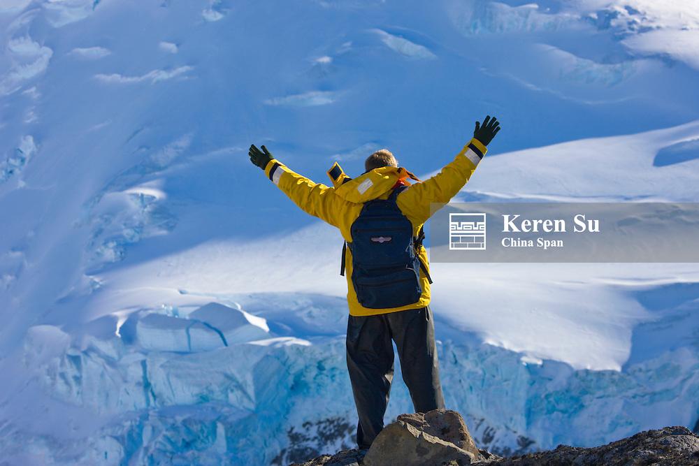 Tourist with iceberg on Half Moon Island, Antarctica