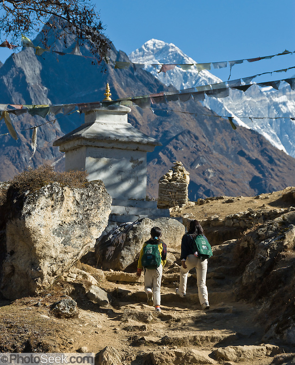 """School children walk towards Khumjung, in Sagarmatha National Park, Nepal, beneath Mount Everest (29,035 feet / 8850 meters elevation above sea level), the highest mountain on Earth. Mount Everest was first called Chomolungma or Qomolangma (""""Goddess Mother of the Earth"""" in Tibetan). In 1865, Andrew Waugh, the British surveyor-general of India named the mountain for his chief and predecessor, Colonel Sir George Everest. In the 1960s, the Government of Nepal named the mountain Sagarmatha, meaning """"Goddess of the Sky"""". The mountain, which is part of the Himalaya range in High Asia, is located on the border between Nepal and Tibet, China. Sagarmatha National Park was created in 1976 and honored as a UNESCO World Heritage Site in 1979."""