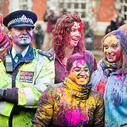 London, UK - 23 March 2013: a policeman poses for a picture with other partygoers during the Holi Spring Festival of Colour that takes place at Orleans House Gallery in Twickenham. The annual event marks the end of Winter and welcomes the joy of spring.