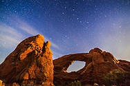 The Big and Little Dippers circling Polaris over South Window Arch in Arches National Park, Utah, with the rising waning Moon lighting the landscape and sky. <br />