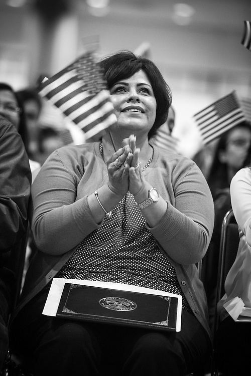 A new American citizen cheer after being sworn in at a makeshift Federal courtroom in the Los Angeles Convention Center. Outside, political activists await the new Americans.
