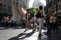 Activists hand out flyers on the streets of Buenos Aires while others go about daily life.