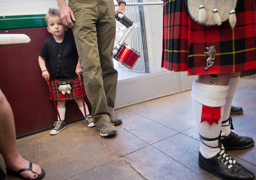 """mkb031617b/metro/Marla Brose --  Duncan Monié, 3, holds onto his drumsticks as he peers out from behind his father, Andrew Monié, to watch his mother, Lorraine McInnes, Pipe Sgt. for High Desert Pipes and Drums, as she performed with the rest of the band members at O'Niell's on Central Ave. during a lunchtime set, Friday, March 17, 2017, in Albuquerque, N.M. """"What's St. Patrick's Day with out bagpipes?"""" asked Bill Horn, Pipe Major for the band, who explained that they had ten performances scheduled throughout the day. (Marla Brose/Albuquerque Journal)"""