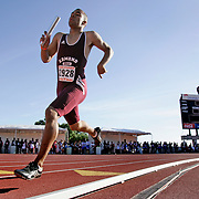 Gordon Butler of Edmond Santa Fe High School in Oklahoma runs his leg of the 4x400-meter relay as the following heats' teams watch in the background.