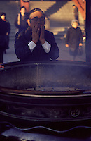 A Japanese man purifies himself with smoke from the incense of a cauldron in the Senso-ji Shrine in Asakusa, Tokyo, Japan.