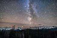 The Milky Way over the region of Athabasca Pass, as seen from the highway viewpoint on the Icefields Parkway, in Jasper National Park, Alberta, Oct 22, 2016. It was this pass that David Thompson used primarily in the later 1700s and early 1800s as his route into BC for extending the fur trade across the Divide. He travelled back and forth across this pass during his employment with the North West Company. His Narratives provides great quote about his experience one winter night on the summit of the Pass: <br /> <br /> &ldquo;My men were not at their ease, yet when night came they admired the brilliancy of the Stars, and as one of them said, he thought he could almost touch them with his hand.&rdquo;<br /> <br /> The Milky Way here is the section through Aquila, with Altair at top and Mars bright above the peaks of the Continental Divide. Illumination is by starlight.<br /> <br /> This is a stack of 8 exposures, mean combined to smooth noise, for the ground and one exposure for the sky, all 25 seconds at f/2 with the Sigma 20mm lens, and Nkion D750 at ISO 6400.