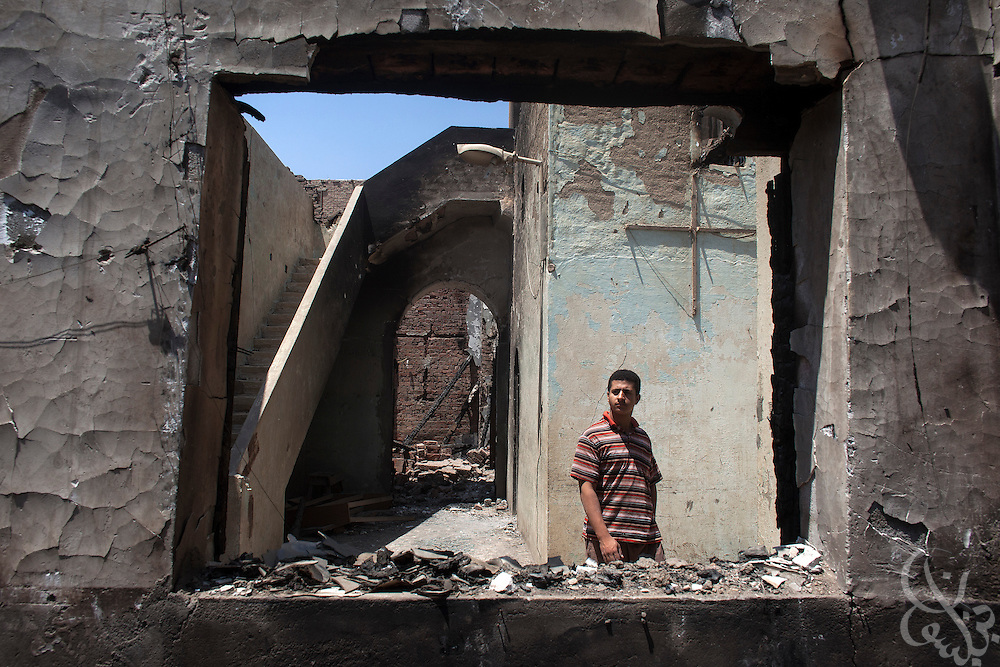 An Egyptian man walks through the burnt and looted ruins of the (old) Virgin Mary Church August 20, 2013 in the village of Nazla, located near el Fayoum, around a 100 kilometers South of Cairo, Egypt.  Christian villagers report 2 churches and a monastery in the area came under attack by their Muslim neighbors on the same day as Egyptian security forces were moving to forcibly disperse the sit-in camp of the supporters of deposed president Mohamed Morsi.