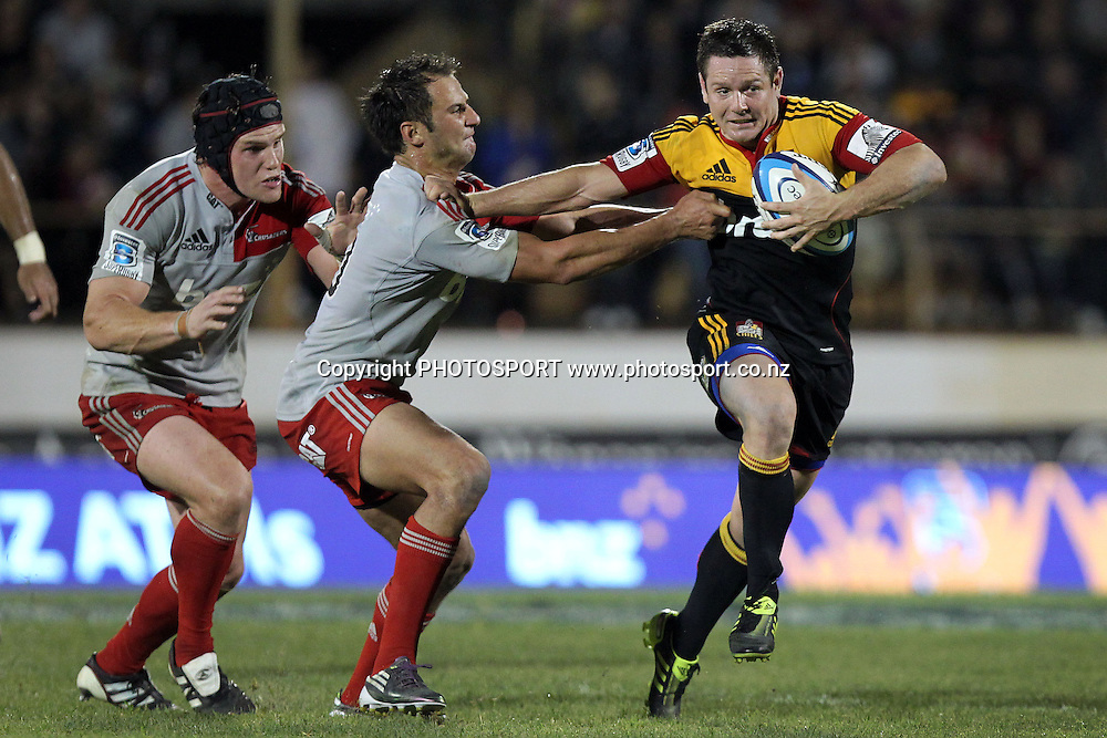 Chiefs' Mike Delany fends against Crusaders' Matt Berquist. Super 15 rugby union match, Chiefs v Crusaders at Baypark Stadium, Mt Maunganui, New Zealand. Friday 15th April 2011. Photo: Anthony Au-Yeung / photosport.co.nz
