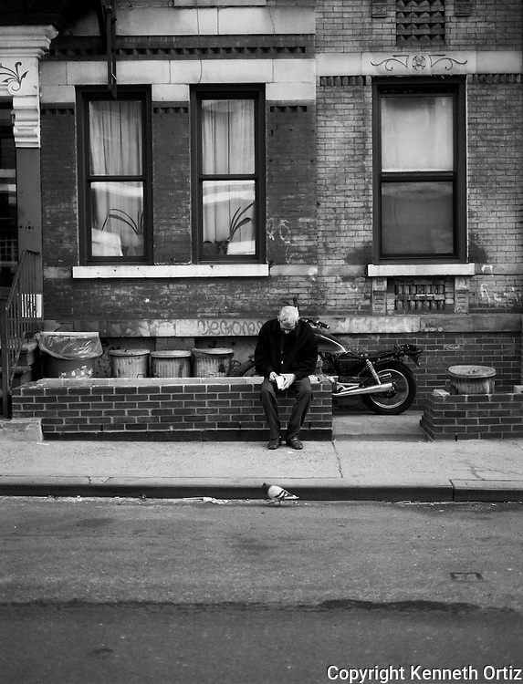 In Astoria Queens a man sits silently contemplating his cup of coffee while a pigeon walks down the street going about his business.