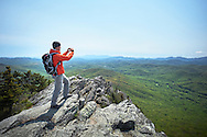 A hiker uses his smartphone to photograph a scenic overlook on the summit of Grandfather Mountain near the Blue RIdge Parkway of North Carolina