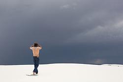 shirtless muscular man walking towards dark clouds in the desert