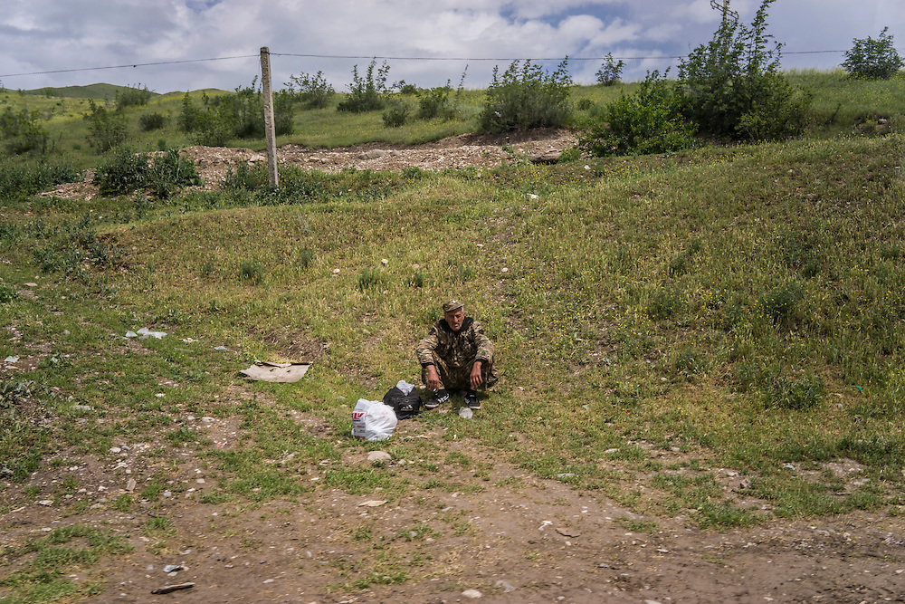 A soldier from Nagorno-Karabakh sits by the road outside a military base on Sunday, May 8, 2016 in Talish, Nagorno-Karabakh.