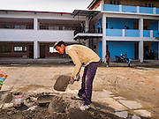 01 MARCH 2017 - KHOKANA, NEPAL: A construction worker at a new school in Khokana. The school, one of the few signs of earthquake recovery, was built after the 2015 earthquake destroyed the original school. Recovery seems to have barely begun nearly two years after the earthquake of 25 April 2015 that devastated Nepal. In some villages in the Kathmandu valley workers are working by hand to remove ruble and dig out destroyed buildings. About 9,000 people were killed and another 22,000 injured by the earthquake. The epicenter of the earthquake was east of the Gorka district.     PHOTO BY JACK KURTZ