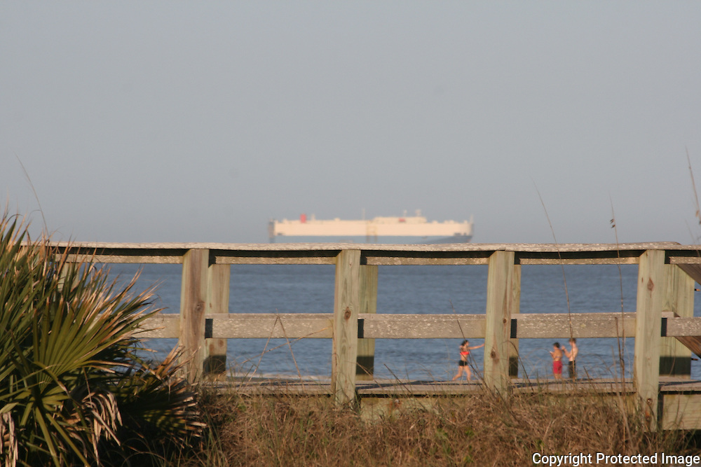 A cargo ship seemingly floating on top of a walkway to Jekyll Island beach with beach goers underneath.