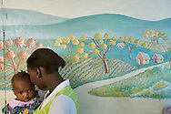 A woman stands with her daughter in front of a mural showing a utopian version of the mountainside above Carrefour, Haiti.  Reality is a stark contrast from the painting on the building behind them.