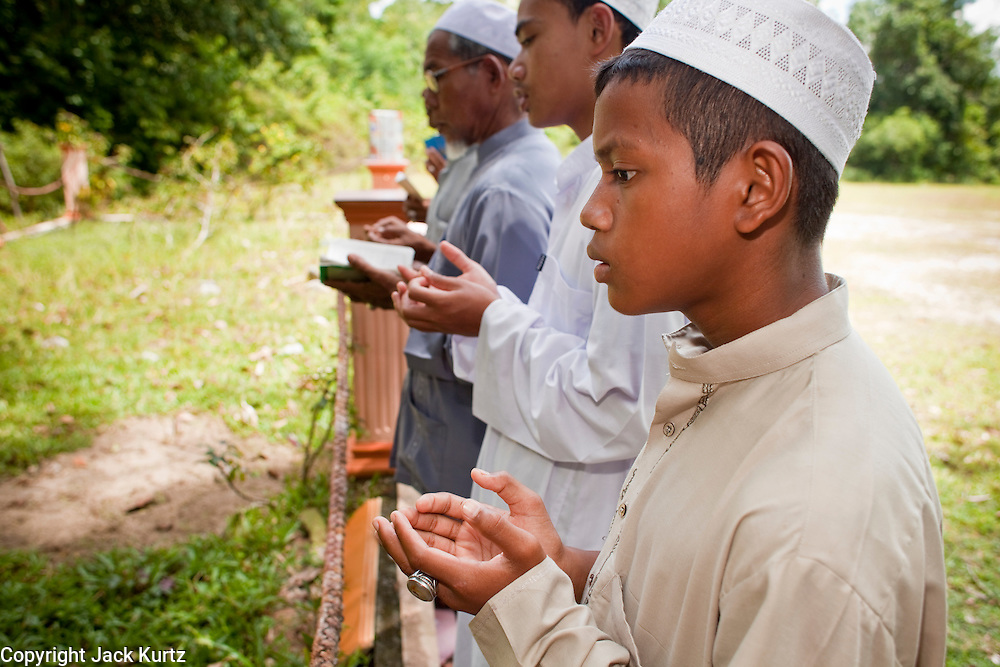 """Sept 27, 2009 -- BACHO, NARATHIWAT: Muslim men pray at a mass grave near the 300 Year Mosque in Bacho, Narathiwat, Thailand, for 22 Muslim men killed by Thai security forces in Oct. 2004. According to local community leaders, many of the men in the grave are unidentified because the bodies were mutilated beyond recognition before they were returned to their families.  Thailand's three southern most provinces; Yala, Pattani and Narathiwat are often called """"restive"""" and a decades long Muslim insurgency has gained traction recently. Nearly 4,000 people have been killed since 2004. The three southern provinces are under emergency control and there are more than 60,000 Thai military, police and paramilitary militia forces trying to keep the peace battling insurgents who favor car bombs and assassination.   Photo by Jack Kurtz / ZUMA Press"""