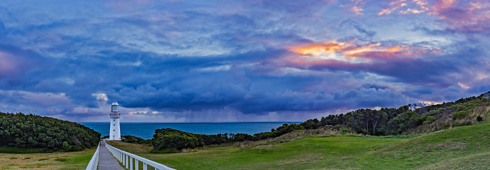 A cloudy sunset at the Cape Otway Lighthouse on the Great Ocean Road, Victoria, Australia, with rain clouds off shore. This lighthouse was built in 1848 but docommissioned in the 1980s and replaced with a smaller beacon out of sight here behind the lighthouse tower. In its day, this lighthouse served as &ldquo;landfall light,&rdquo; the first light the immigrant ships of the 1880s would see after a long sea voyage. <br /> <br /> This is a panorama of 4 segments with the 35mm lens and Canon 6D; Stitched with Adobe Camera Raw.