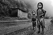 Children in the mist and rain near their village in the mountains near Luang Prabang, Laos.<br /> Winner of first place in the Chilsd portrait category of 'Prix de le Photographie Paris'2013
