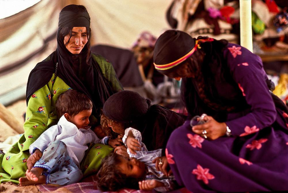 Shammar women wear decorative tattoos on their faces and hands. Here they play with their children. The Nafud, Saudi Arabia