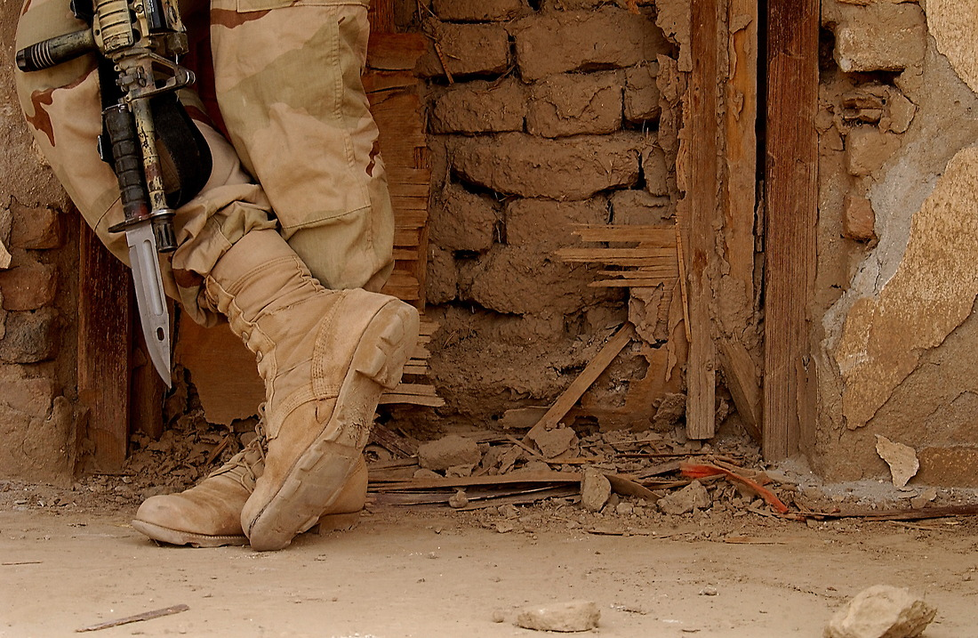 """A member of the U.S. Army 3/187th Scouts from Fort Campbell, KY, takes a break at a bombed out building on April 12, 2002,  at  Kandahar Air Base, Afghanistan. The Scouts, and the Lord Strathcona's Force (Royal Canadian) Reconnaissance Squadron """"RECCE"""" 2TP from Edmonton Canada, along with the Afghanistan Military Forces (AMF) have been conducting surveillance of the outer perimeter of the Air Base. This small multinational force is positioned at the North Tower on the outer perimeter outside of Kandahar airport during Operation Enduring Freedom. Their mission is to play a surveillance role on the outer perimeter with the capability of providing direct fire support. Kandahar Airport is home to over 5000 U.S. and Multinational Armed Services. — © SSgt Jeremy Lock/"""