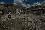 RENDEL, HAITI - OCTOBER 12, 2016: A young boy carries water he fetched from the river to what remains of his family's home in Rendel. A week has passed since Hurricane Matthew tore through this remote stretch of Haiti's southern peninsula, leaving an apocalyptic landscape of treeless countryside, disarticulated homes and a land stripped of its natural riches.  But for many, the torment has only started. What began as a small cholera outbreak in the mountains before the hurricane has now spread into every crevice of this vally and the hills above.  PHOTO: Meridith Kohut for The New York Times