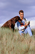 man reading a book with his dog sitting next to him outdoors in a field