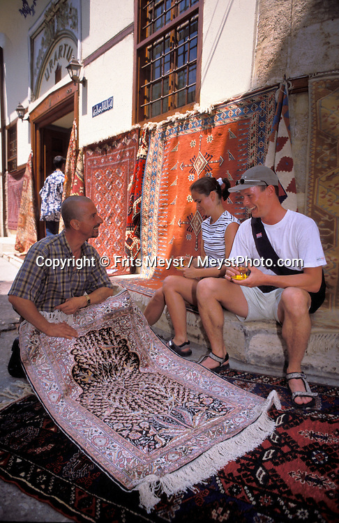 Antalya, Turkey, 2004. Tourists drink Turkish tea in one of the many carpetshops in the historical center of Antalya. Many holidaymakers find their way to the Turkish riviera to enjoy the sun and Turkish hospitality. Photo by Frits Meyst/Adventure4ever.com