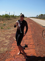 Bicycle rider tries to cool down while cycling through the Great Sandy desert