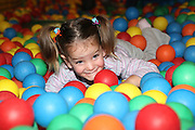 Indoor children's playground young child plays in a ball pool