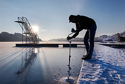 Ice fishing at frozen lake Viljandi, Estonia. Fisherman drilling hole, diving tower.