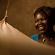 Minata Ouedraogo (38), with the mosquito net she shares with her children at her home in the village of Songodin in the Sanmatenga region of Burkina Faso on 25 February 2014. Mosquito nets greatly decrease the incidence of malaria by reducing the risk of being bitten by the nocturnal Anopheles mosquito, which carries the malaria parasite.