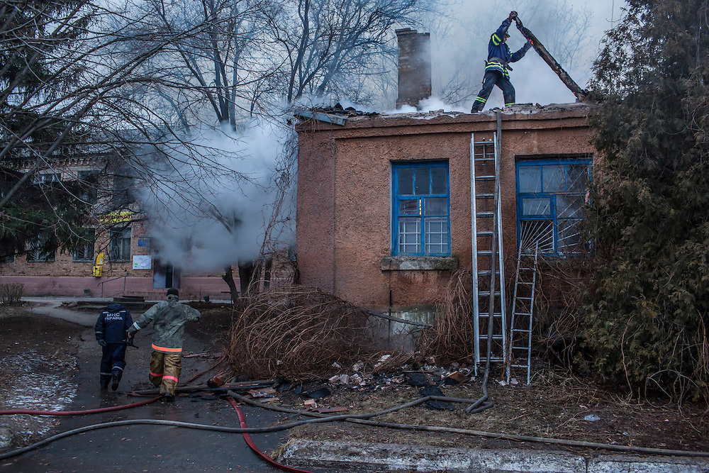 ARTEMIVSK, UKRAINE - FEBRUARY 14: Firefighters battle a blaze at a medical clinic which was hit by artillery on February 14, 2015 in Artemivsk, Ukraine. The clinic was closed and there were no reported casualties. A ceasefire between Ukrainian forces and pro-Russian rebels is scheduled to go into effect at midnight. (Photo by Brendan Hoffman/Getty Images) *** Local Caption ***