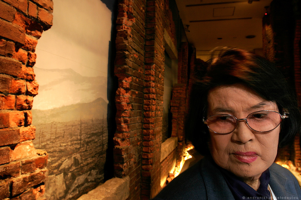 "MICHIKO YAMAOKA: Hiroshima A-Bomb survivor, standing in front of a reproduction of a bombed building, inside the Peace Memorial Museum.  Yamaoka was 15 and also worked at the telephone exchange when the bomb fell as she was on her way to work.  She was badly injured and would have died under a wall that collapsed on her, if her mother had not come to her rescue. Her face was so badly disfigured by the injuries she wanted to die but her mother helped her regain the will to live. Later she went to the US and had 27 operations on her damaged face and body. "" I can't believe the world is still trying to develop nuclear weapons"", she says.  ""I wish they could all see me""."