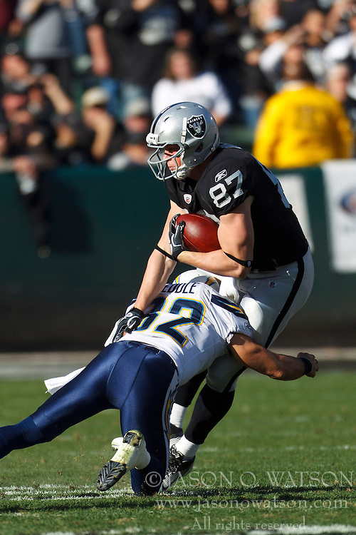 Jan 1, 2012; Oakland, CA, USA; Oakland Raiders tight end Kevin Boss (87) is tackled by San Diego Chargers free safety Eric Weddle (32) during the second quarter at O.co Coliseum. Mandatory Credit: Jason O. Watson-US PRESSWIRE