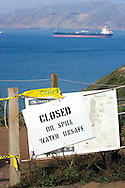 Beach and water closure signs are posted stemming from the November 7, 2007 oil spill, in San Francisco bay. A tanker ship exiting the San Francisco bay is seen in the background.