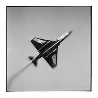 USA, Florida, Pensacola, Blurred black and white image of US Navy Blue Angels fighter jet above highway roadside stop on summer aftenroon