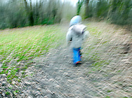 Young Boy Running Through Woods