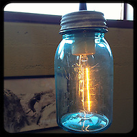 USA:California:San Bernadino County:Joshua Tree: A blue glass Mason Jar hanging restaurant table light at the Crossroads Cafe in Joshua Tree, California provides a sense of nostalgia in the desert.