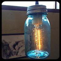 USA:California:San Bernadino County:Joshua Tree: A blue glass Mason Jar hanging restaurant table light at the Crossroads Cafe in Joshua Tree, California provides a sense of nostalgia in the desert.