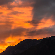 Orange sunset light on clouds over Alpamayo Valley in the Cordillera Blanca, Andes Mountains, Peru, South America. Day 7 of 10 days trekking around Alpamayo in Huascaran National Park (UNESCO World Heritage Site).
