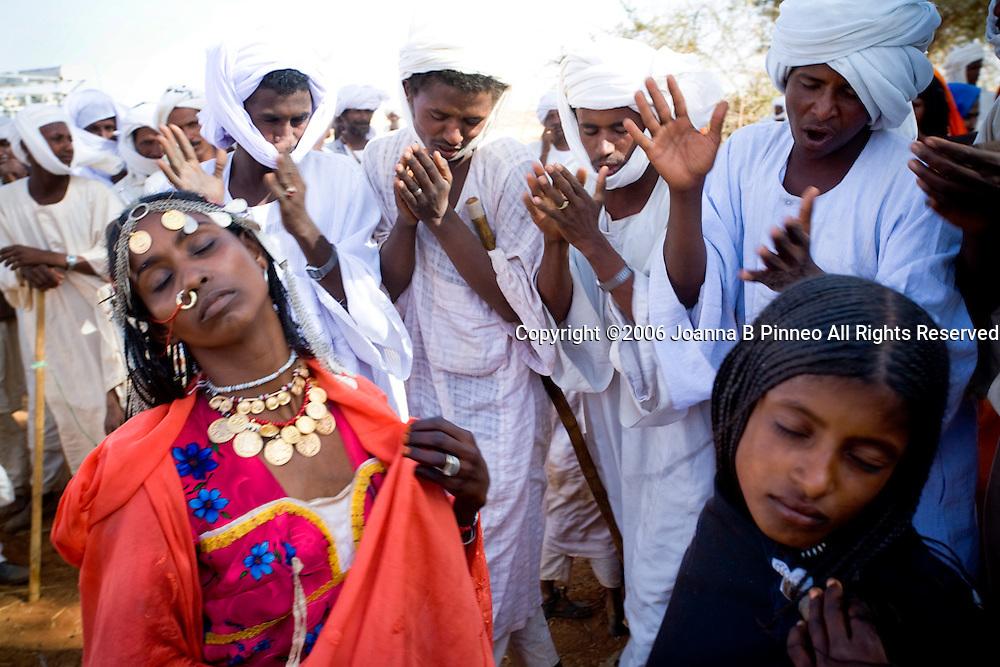 Shanabla men dance and chant at a wedding celebration near El Obeid, Sudan. A nomadic tribe they raise camels.