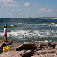 Lady fishing on the jetty at Mustang Island State Park on the central coast of Texas in the late summer.